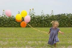 Niño feliz que se ejecuta con los globos en campo imagen de archivo libre de regalías