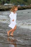 Niño feliz que se ejecuta en el océano Fotografía de archivo