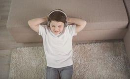 Niño feliz que se relaja con los auriculares en casa Foto de archivo