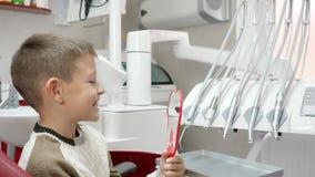 Niño feliz que se sienta en silla dental y que mira en espejo en fondo del equipo moderno almacen de metraje de vídeo
