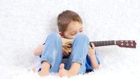 Niño feliz que toca una guitarra acústica de los niños, sonrisa, sentándose en un sofá blanco almacen de video