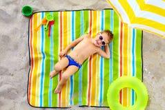 Niño feliz que toma el sol en la playa colorida Fotografía de archivo libre de regalías