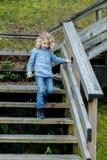 Niño feliz que va abajo de las escaleras de madera Fotos de archivo
