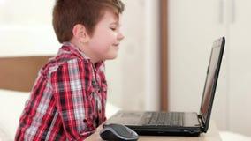 Niño feliz skyping vía el ordenador portátil, niño sonriente en casa, niño pequeño que mira historietas divertidas en el artilugi almacen de metraje de vídeo