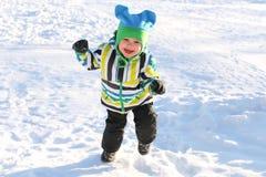 Niño feliz sonriente que corre en invierno al aire libre Foto de archivo libre de regalías