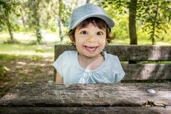 Niño feliz travieso activo al aire libre sonriente sorprendido de la gorra de béisbol alegre del bebé de los niños foto de archivo libre de regalías