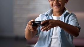 Niño feliz y alegre que ríe jugando la nueva videoconsola por la primera vez, ocio imágenes de archivo libres de regalías