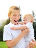 Niño feliz y bebé al aire libre Foto de archivo