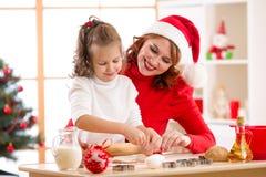 Niño feliz y madre que cuecen las galletas de Navidad juntas en el sitio adornado festivo Imagenes de archivo