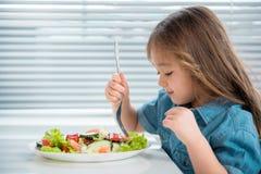 Niño femenino alegre que come verduras tajadas Foto de archivo libre de regalías
