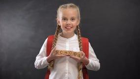 Niño femenino alegre que sostiene los cubos de madera con palabra de la escuela, niño del escolar de primer año metrajes