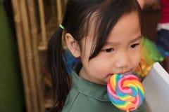 Niño femenino asiático con la lamedura de la piruleta del arco iris Fotos de archivo libres de regalías