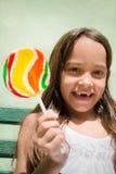 Niño femenino bonito con la sonrisa del lollipop Fotos de archivo libres de regalías