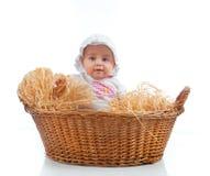 Niño femenino lindo en una cesta de la paja imagen de archivo