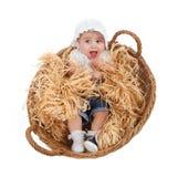 Niño femenino lindo en una cesta de la paja Fotografía de archivo