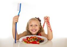 Niño femenino lindo que come el plato por completo de dulces y que sostiene el cepillo de dientes enorme en concepto del cuidado  fotos de archivo libres de regalías