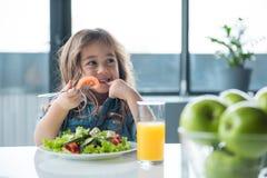Niño femenino lindo que desayuna sano Imagen de archivo