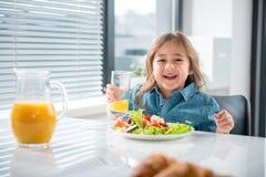 Niño femenino lindo que desayuna sano en casa Imagen de archivo
