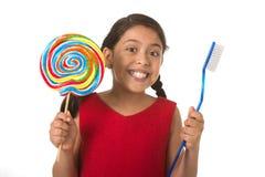 Niño femenino lindo que sostiene el caramelo espiral grande de la piruleta y el cepillo de dientes enorme en concepto del cuidado fotografía de archivo