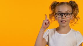 Niño femenino listo en los vidrios que tienen idea, curiosidad del conocimiento, plantilla, primer metrajes