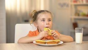 Niño femenino que come el buñuelo sabroso, vidrio de leche en la tabla, bocado dulce, nutrición almacen de metraje de vídeo
