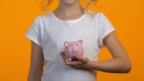 Niño femenino que pone monedas en la hucha, los ahorros y el presupuesto personal, finanzas almacen de metraje de vídeo