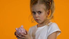 Niño femenino trastornado shacking la hucha vacía, falta de dinero pobre del presupuesto personal almacen de metraje de vídeo