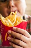 Niño hambriento que sostiene las patatas fritas Imagen de archivo libre de regalías
