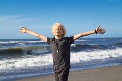 Niño hermoso con concepto extendido de la libertad de los brazos foto de archivo