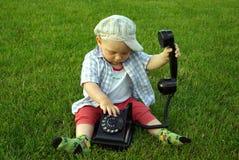 Niño hermoso con el teléfono a disposición en GR verde Imagen de archivo libre de regalías
