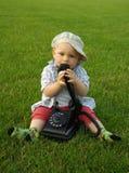 Niño hermoso con el teléfono en la hierba verde Foto de archivo libre de regalías