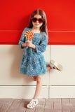 Niño hermoso de la niña con la piruleta que lleva un vestido y las gafas de sol del leopardo sobre rojo Foto de archivo libre de regalías