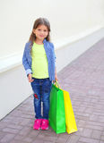 Niño hermoso de la niña con los panieres que camina en ciudad Fotos de archivo libres de regalías