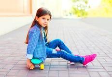Niño hermoso de la niña del retrato que se sienta en el monopatín Foto de archivo libre de regalías