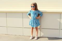 Niño hermoso de la niña que lleva un vestido y las gafas de sol del leopardo sobre blanco Fotos de archivo