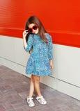 Niño hermoso de la niña que lleva un vestido y las gafas de sol del leopardo sobre rojo Imagen de archivo libre de regalías
