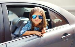 Niño hermoso de la niña que se sienta en el coche, mirando hacia fuera la ventana Fotos de archivo libres de regalías