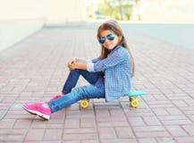 Niño hermoso de la niña que se sienta en el monopatín Imagen de archivo libre de regalías