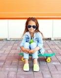Niño hermoso de la niña que se sienta en el monopatín Fotos de archivo libres de regalías