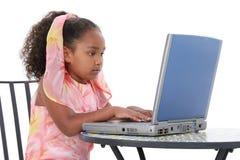 Niño hermoso de seis años que trabaja en la computadora portátil Foto de archivo libre de regalías