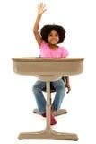 Niño hermoso del afroamericano que se sienta en un escritorio foto de archivo libre de regalías