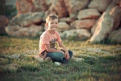 Niño hermoso del muchacho que presenta en el verano Central Park en la hierba fresca verde que lleva sombras elegantes de la ropa Imagen de archivo libre de regalías
