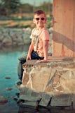 Niño hermoso del muchacho que presenta en el verano Central Park en la hierba fresca verde que lleva sombras elegantes de la ropa Fotos de archivo