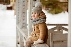 Niño hermoso muy bonito de la muchacha en una capa beige y un sombrero gris SM Fotografía de archivo