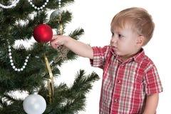 Niño hermoso que adorna el árbol del Año Nuevo Fotografía de archivo