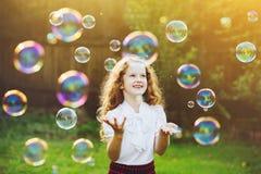 Niño hermoso que goza soplando burbujas de jabón en el verano en n imagenes de archivo
