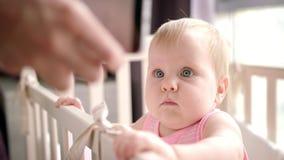 Niño hermoso que mira el teléfono móvil Bebé que mira smartphone en pesebre metrajes