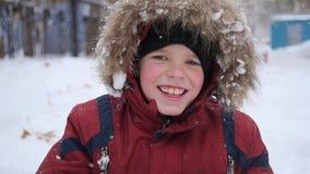 Niño hermoso que sonríe en el parque del invierno Está nevando metrajes