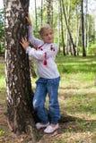 Niño iby un abedul en un bosque Foto de archivo