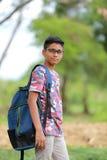 Niño indio en la lente con el bolso de escuela Foto de archivo libre de regalías